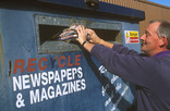 Man recycling newspaper in bring bank