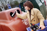 Woman recycling glass bottles at bottle bank
