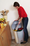 Woman putting newspaper in compartmentalised kitchen recycling bin