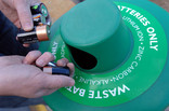 Putting batteries into green waste battery recycling bin