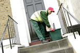 Recycling crew member collecting kerbside recycling bin - front of house