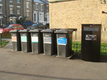 Row of black recycling wheelie bins on residential street
