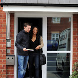 Couple leaving front door of flats