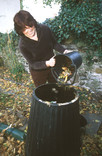 Woman putting food waste into compost bin