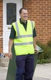 Man collecting green recycling wheelie bin outside house