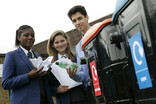 School pupils recycling paper and plastic bottles at outdoor recycling bins