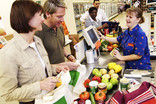Men and women packing food shopping at checkout in re-usable fabric bags