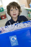 Boy with school paper recycling bin