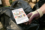 Crew member with black bin bags and 'Sorry we cannot recycle' information leaflet
