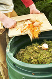 Man scraping veg peelings from chopping board into compost bin