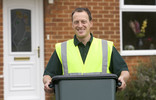 Man collecting green recycling container outside house