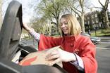 Woman recycling pizza box at bring bank