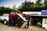 Father and son with fridge freezer to recycle at fridges and freezers recycling point