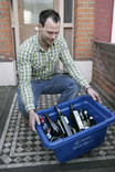 Man putting blue recycling container with glass out for kerbside collection