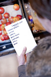 Woman with shopping list in supermarket