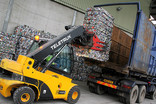 Forklift loading bales of crushed cans onto lorry