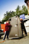 Two men lifting large fridge freezer at fridges and freezers recycling point