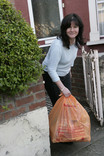 Woman putting orange recycling bag out for collection