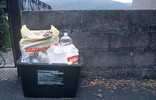 Full recycling bin on street with plastic bottles and paper in carrier bags