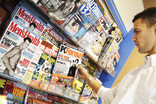 Man choosing magazine in supermarket