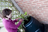 Woman putting garden trimmings into compost bin