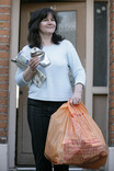 Woman putting recycling out for kerbside collection - orange recycling bag, newspaper and cans