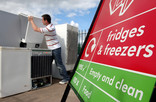 Man recycling fridge freezer and recycling centre