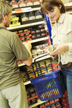 Man and woman choosing tinned food in supermarket