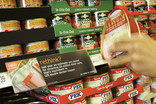 Choosing tinned ham in supermarket with recycling information on shelf label