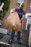 Man putting out orange recycling bag for kerbside collection