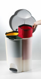 Removing container from compartmentalised kitchen recycling bin, white background