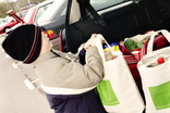 Boy putting re-usable bags of shopping into car boot
