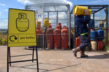 Man recycling yellow gas canister at recycling centre