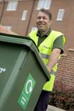 Man with green garden waste wheelie bin