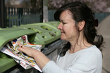 Woman recycling leaflets and catalogue at bring bank