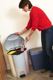 Woman putting newspaper in compartmentalised kitchen recycling bin with waste bin alongside