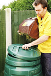 Man emptying box of grass cuttings into green plastic compost bin