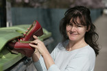 Woman recycling red shoes at bring bank
