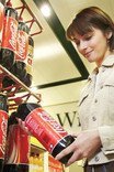 Woman choosing plastic bottle of Coca Cola in supermarket