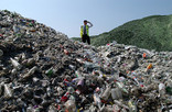 Man standing on mounds of bottles