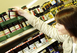 Woman choosing jar of jam in supermarket