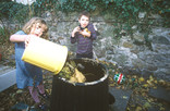 Boy and girl putting garden waste into compost bin