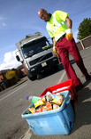 Man collecting red and blue separated recycling bins with recycling lorry