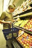 Man choosing apples in supermarket