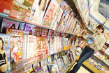 Women reading magazine by shelves of magazines in supermarket