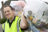 Man collecting clear recycling sacks over shoulder