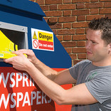 Man recycling Yellow Pages at bring bank