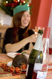 Woman at Christmas dinner table - Christmas pudding, wine bottles, party hats