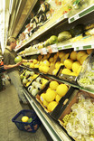 Man choosing melons in supermarket