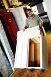Man moving second-hand chest of drawers in warehouse